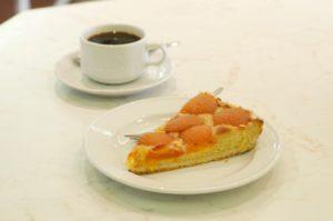 Stück Mailänder Aprikosenkuchen mit Tasse Kaffee